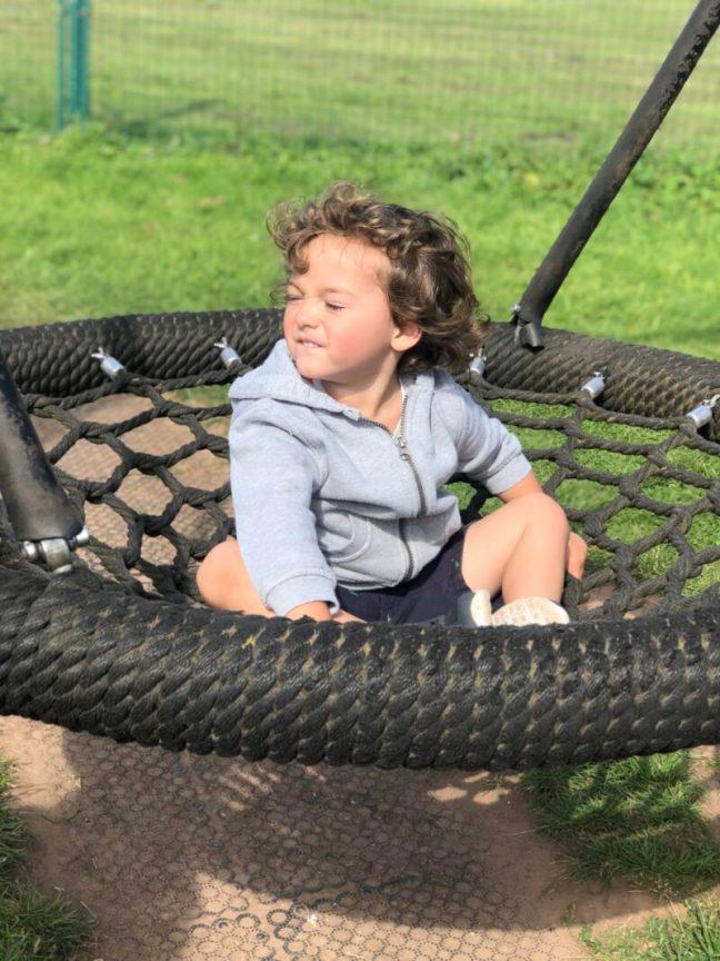 A toddler boy sitting on a basket swing