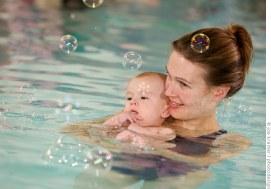 Mutter mit Kind freuen sich an den Seifenblasen. Schwimmschule 32 in Osnabrück. © Joe Kramer