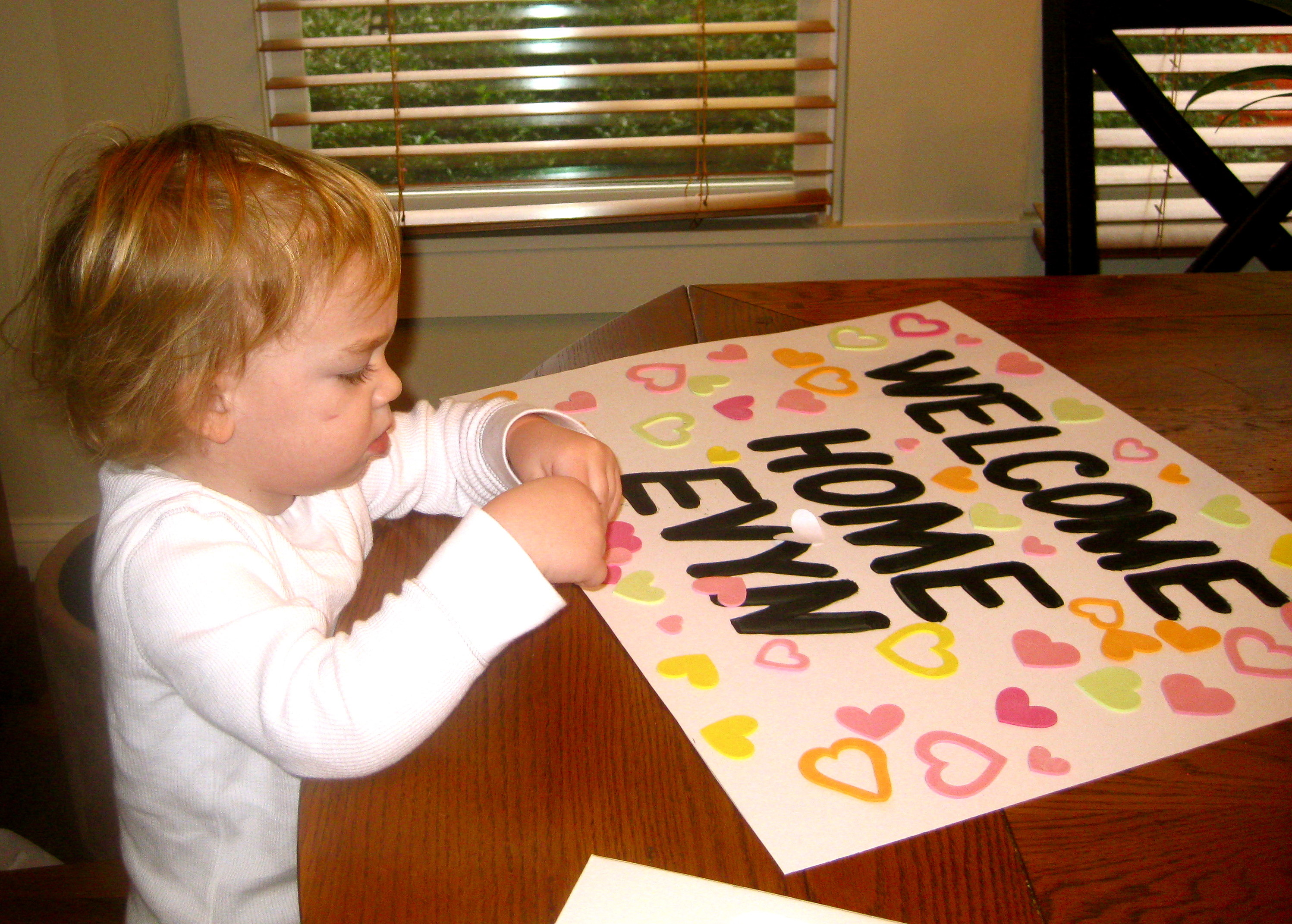 making a sign to welcome home baby sister