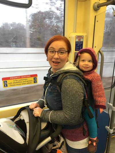 [Image of a white woman with short red hair and glasses smiling at the camera while wearing her white toddler on her back in a Soul brand linen soft structured carrier. The toddler has long curly blonde hair and is smiling at something off camera. They are traveling on a light rail train car and the woman is holding a large stroller in front of her that contains the convertible car seat they are bringing with to the airport. Both mother and child are dressed in autumn weather clothing.]