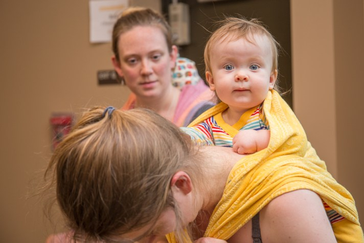 [Image of a wide-eyed baby on a caregiver's back in a sunshine yellow woven wrap. The caregiver is bent over holding on to the to ends of the wrap while a Volunteer Babywearing Educator spots her.]