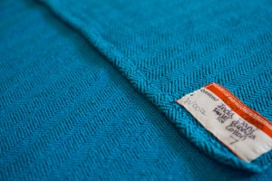 [bright teal woven wrap with a black chevron pattern; the woven wrap has an orange lending library tag sewn onto it]