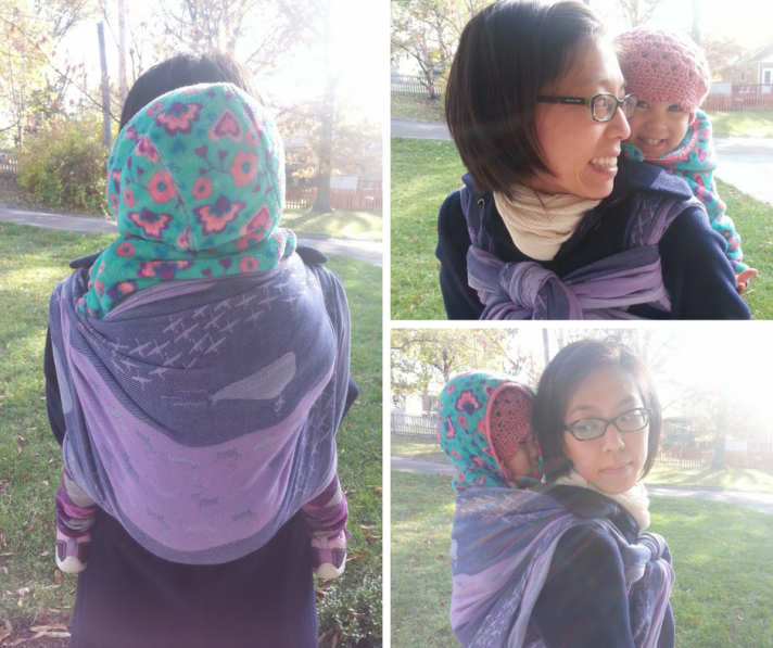 [Three image collage of a smiling tan skin bespectacled Asian woman with short dark brown hair. She's wearing a toddler on her back who is in a green floral fleece with the hood up over a cotton crocheted hat. They're using a purple whale patterned woven wrap carrier. The woman has on a navy wool peacoat and cream-colored scarf around her neck. Image on the left is of the back showing the one layer across toddler's back and purple argyle leg warmers over toddler's legs. Image on the top right is of the woman turned to smile at the toddler's smiling face over woman's shoulders; the wrap is tied Tibetan across the woman's chest. The bottom right image is of the side view with toddler's eyes almost shut from their lovely walk outside.]