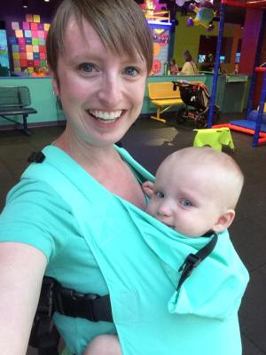 Image of a smiling white woman wearing her fussy infant in an aqua colored solar Connecta soft structured carrier in a children's play area.