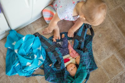 Image of a toddler sitting on the ground with a blue buckle onbuhimo laid out and two dolls inside. Next to the carrier is a blue and white ikat scarf.
