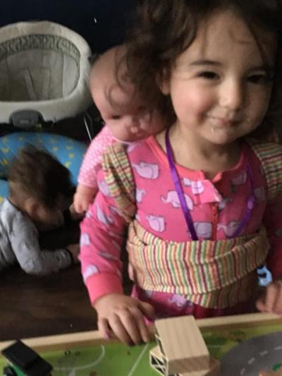 a tan girl with curly brown hair wearing pink pajamas smiling. She has a brown baby on her back. In the background is a blurry brown curly haired tan baby laying on the floor.