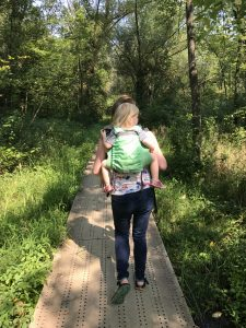 Image of a white woman from behind. She is wearing a white, blonde toddler on her back in a lime green onbuhimo. The background features a marsh and tall, lush trees.