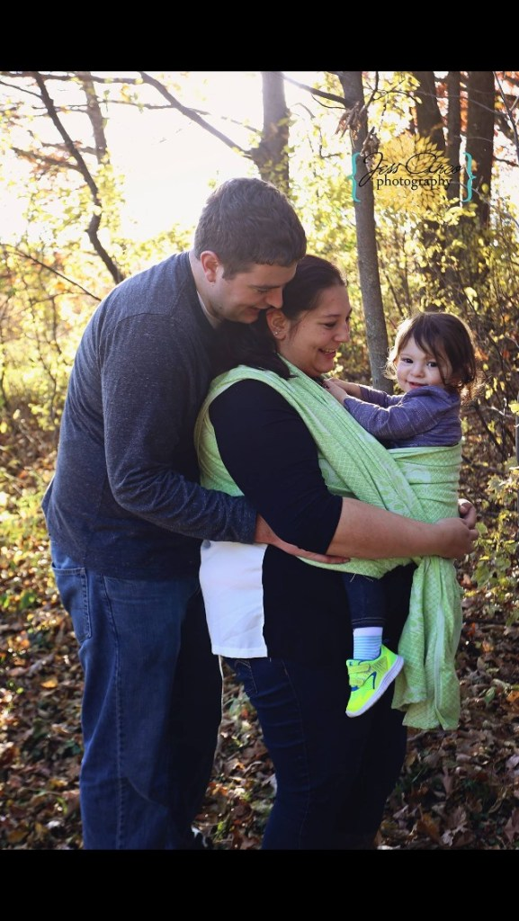 A white man with brown hair hugging a tan pregnant woman with glasses. On the woman's chest is a tan toddler in a lime green wrap. They are standing out in the woods.
