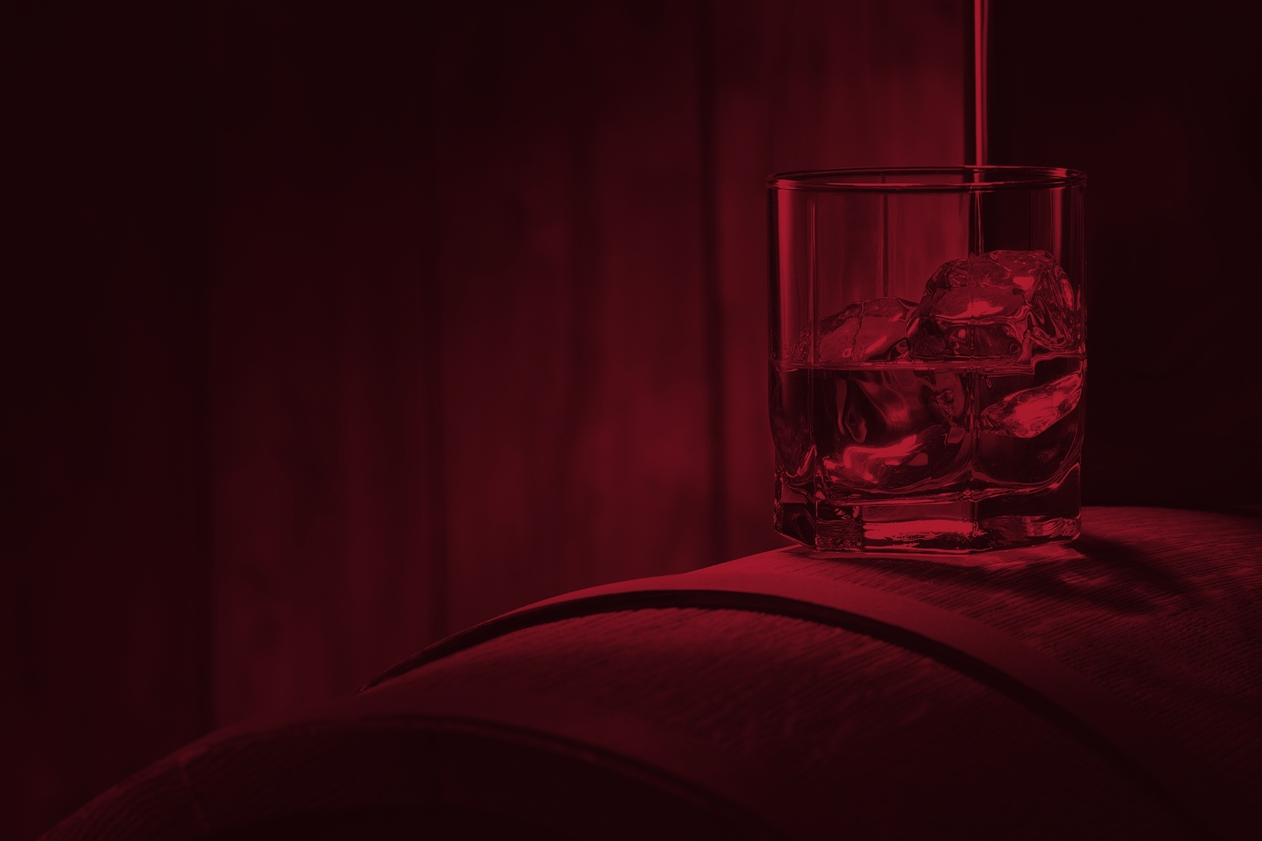 alcohol and ice in a rocks glass on top of a wooden barrel with red image overlay