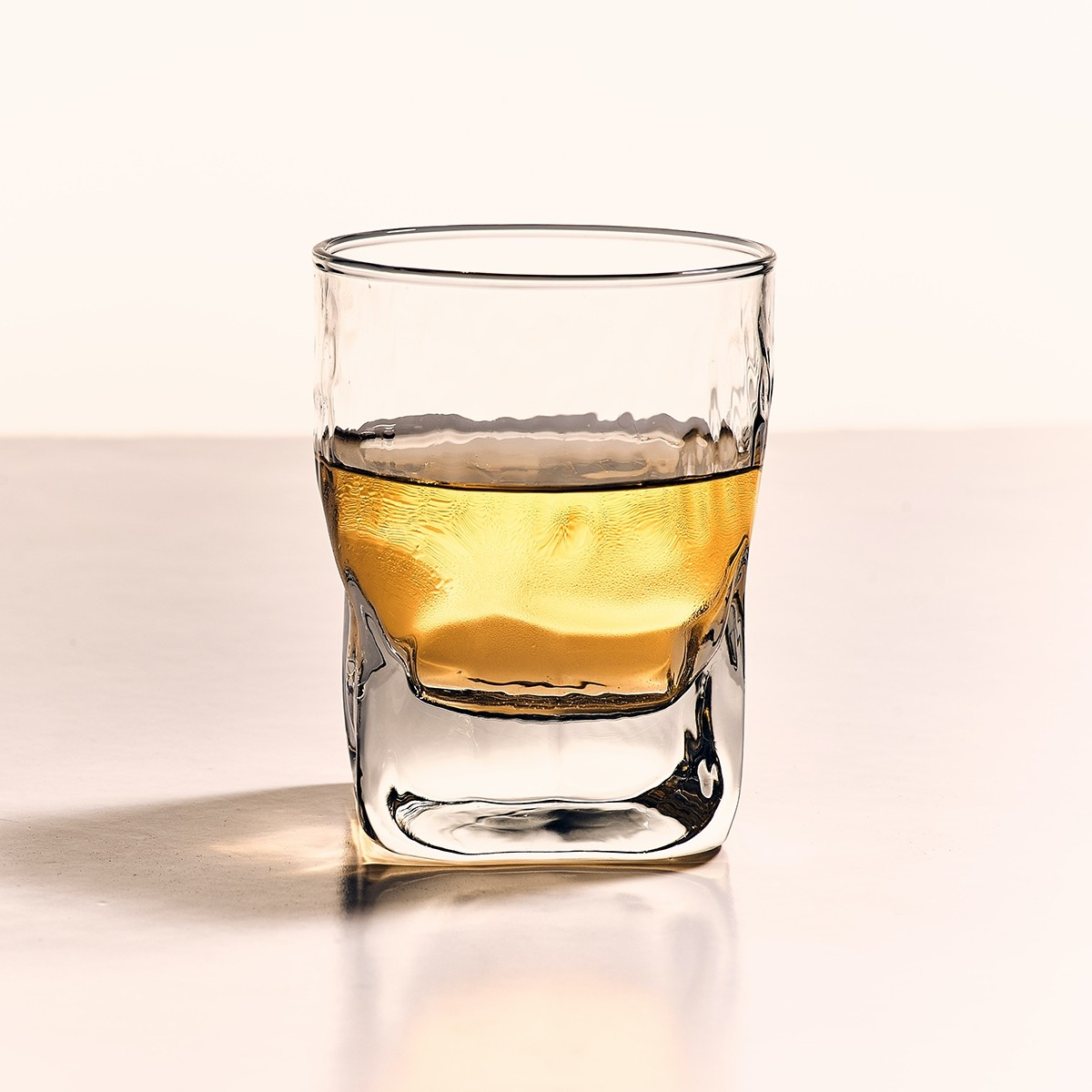 golden alcoholic spirit in a glass on a clean beige surface