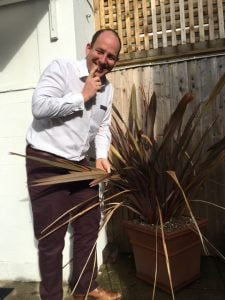 Image shows James Revell - Doctor of chiropractic getting to grips with the patio plants outside of the Lushington Chiropractic X-Ray Suite here in Eastbourne.