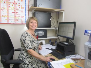 Blog on clinic assistants. Image shows Carole seated at the computer