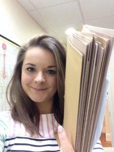 Image shows Chiropractor Dr Caroline Mulliner holding a pile of folders