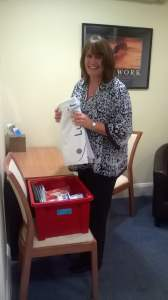 Blog on clinic assistants. Image shows clinic assistant Judy putting items into a red plastic box.