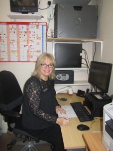 Blog on clinic assistants. Image shows Theresa seated at the computer