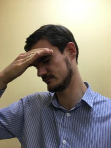 Image shows Doctor of Chiropractic at Lushington Chiropractic in Eastbourne holding his brow with his eyes. In his blog he talks about different types of headache