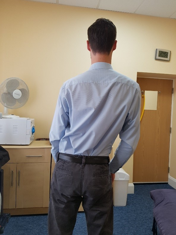 Photo demonstrates a man from behind with the upper part of the back and ribcage moving over to the right in relation to the low back and pelvis.