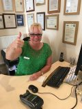 Image shows clinic assistant at Lushington Chiropractic, seated behind the reception desk giving a thumbs up sign.