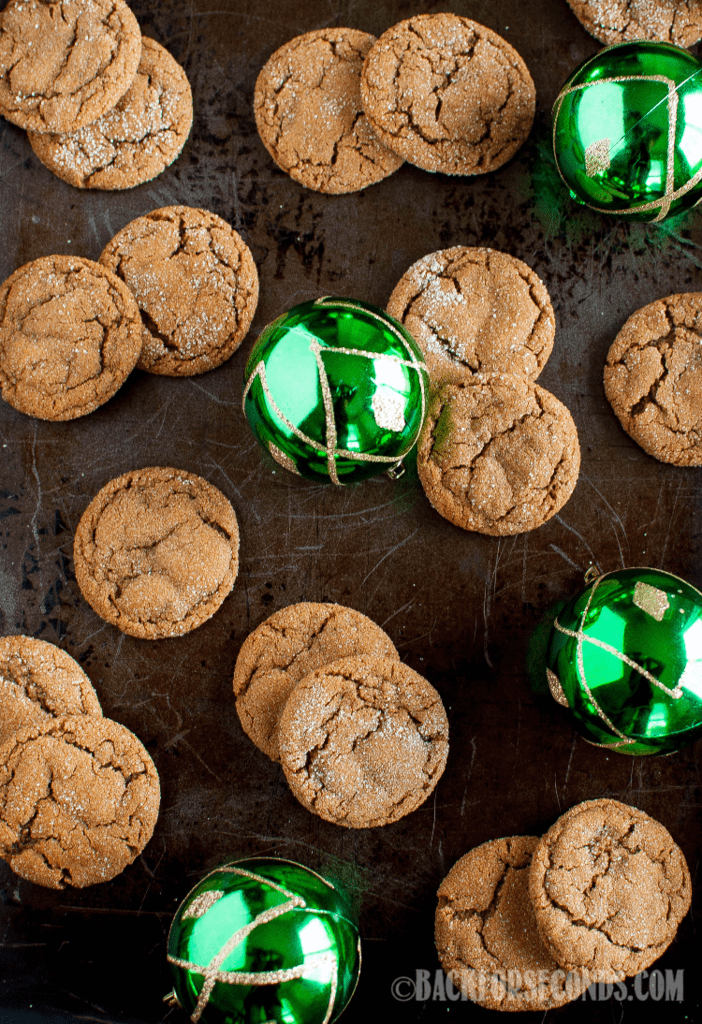 Chewy Molasses Crinkle Cookies scattered on a baking sheet with green ornaments