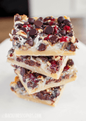 Dark Chocolate Cranberry Magic Bars stacked on a white plate