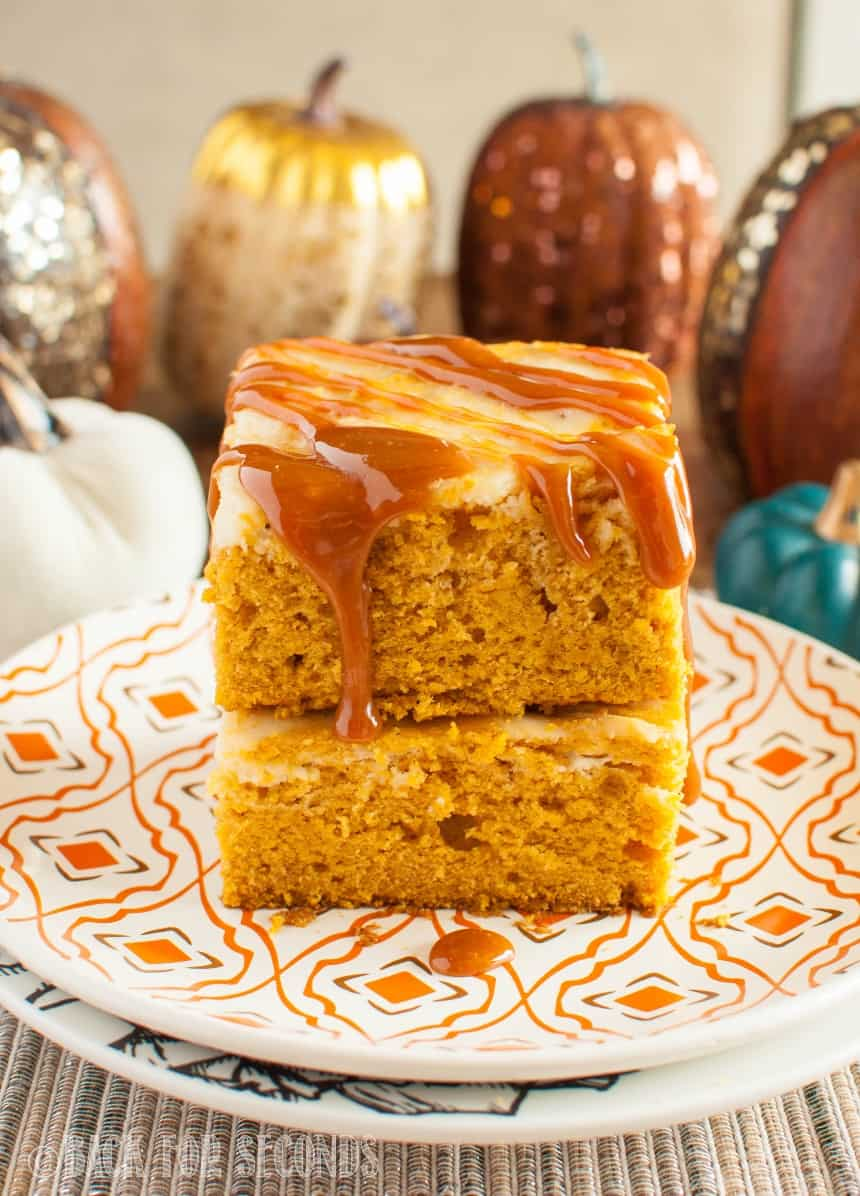 Pumpkin Cheesecake Caramel Bars stacked on a plate with fall decor in the background