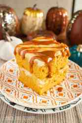 Pumpkin Cheesecake Swirl Bars drizzled with caramel on a fall plate