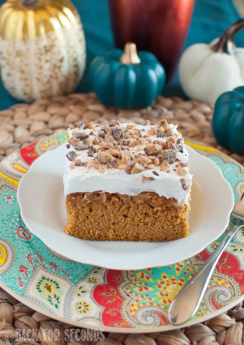Pumpkin Butterscotch Poke Cake sprinkled with toffee on a white plate