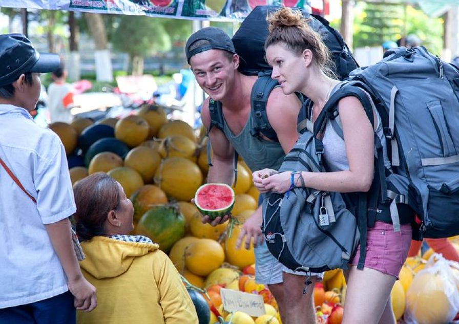 市場で果物を買うバックパッカー