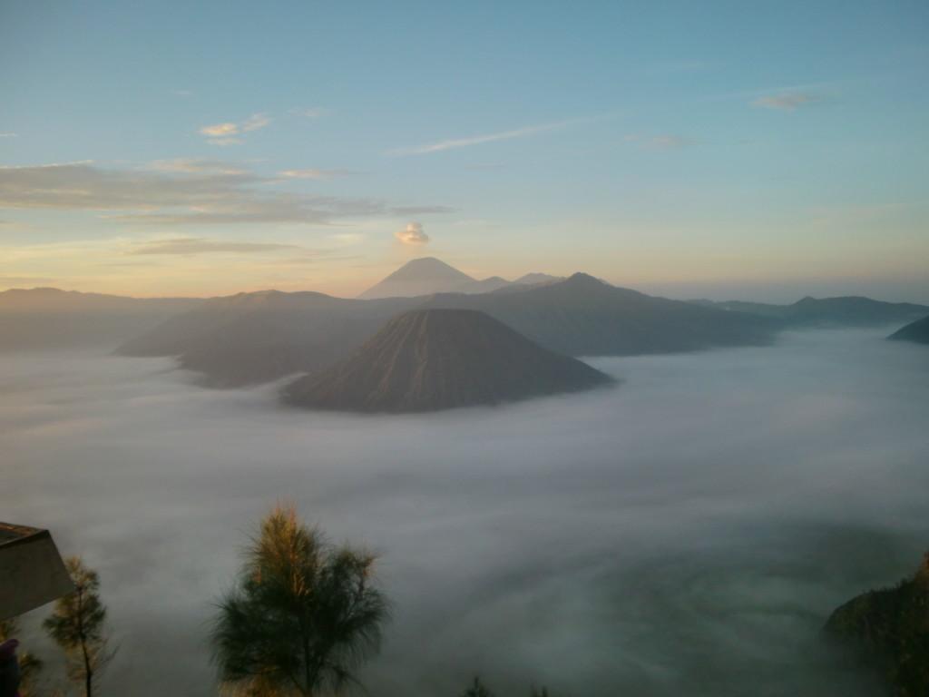 『緑色のバトゥッ山』、『噴煙を舞い上げるブロモ山』、『巨大なクルシ山』、『紫色の神々の座スルメ山』を望む光景
