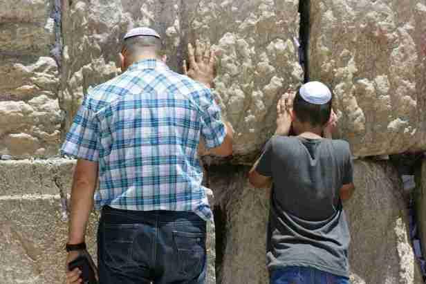 Men praying next to the Western Wall