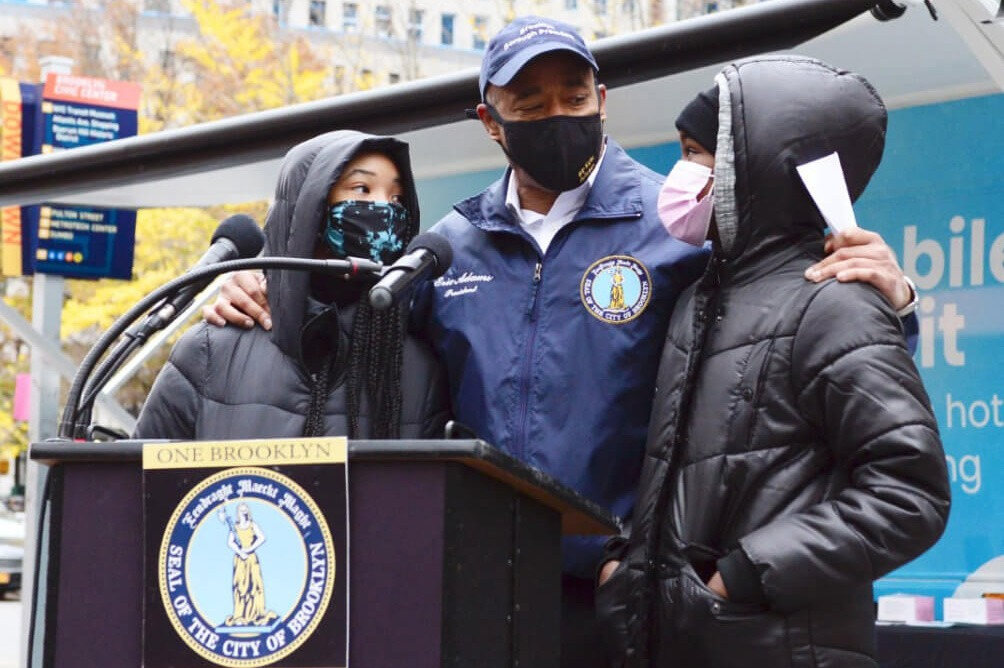 Brooklyn Borough President Eric Adams with two Brooklyn residents at unveiling of first shower bus at Borough Hall in Downtown Brooklyn. Erica Krodman/Brooklyn BP's Office