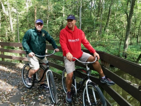 two men on bikes in a forest