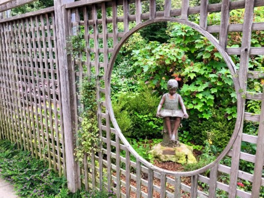 garden statuary through a fence window