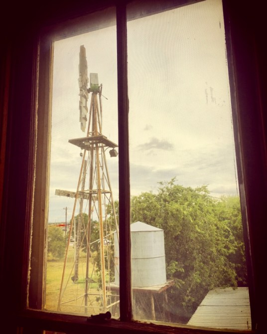 windmill and water tank through a window with a vintage photo filter