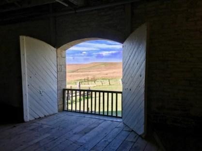 view of prairie and sky through barn door