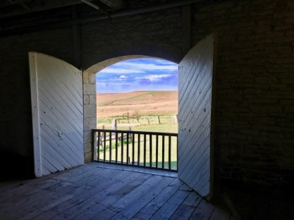 view of prairie and sky through barn door