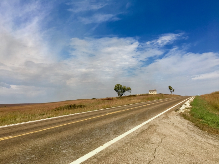 Kansas Flint Hills Scenic Byway road and distant schoolhouse
