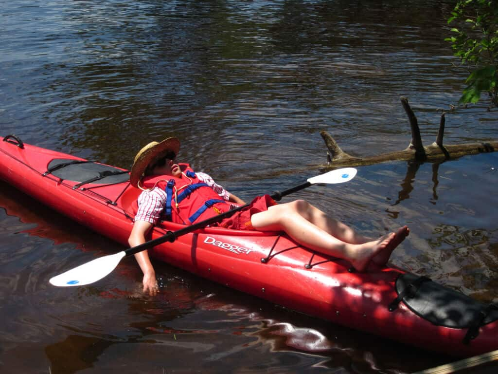 A lazy kid snoozing on a red kayak