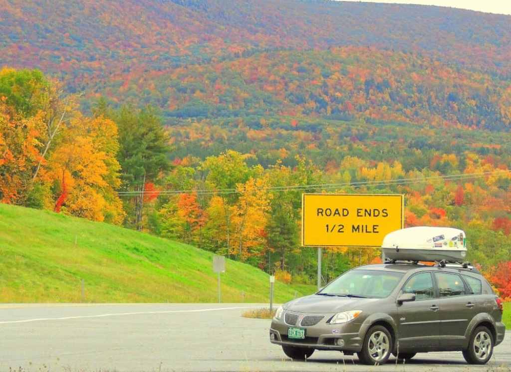 A grey compact car parked near a sign that says Road Ends 1/2 mile. Beautiful forests of fall foliage in the background