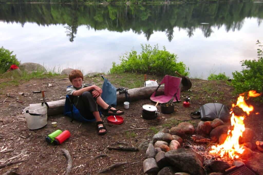 Easy Camping Meals for Your Family: A young boy sits near a campfire. There is a lake in the background.