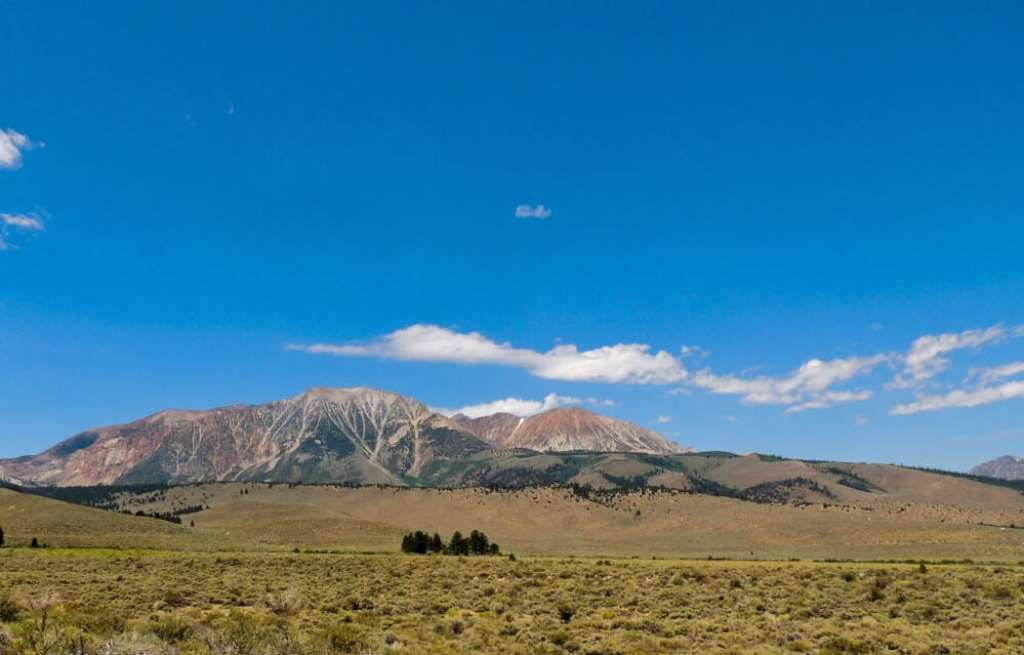 A field with distant mountains and a bright blue sky in Tonopah, NV