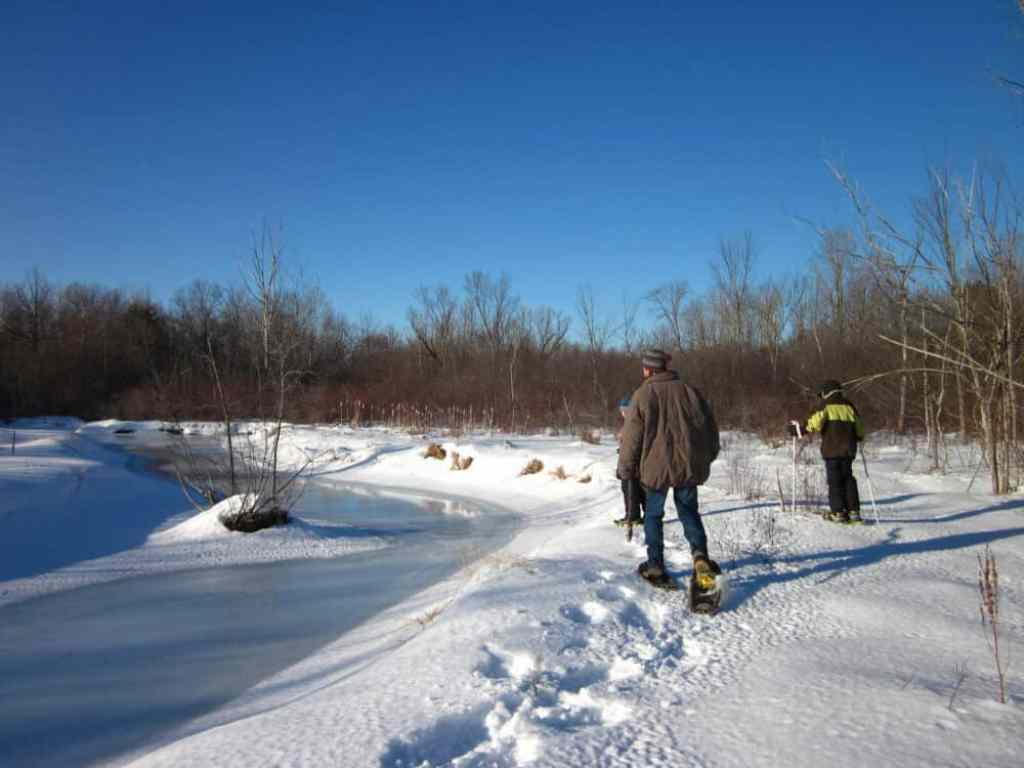 A man and two kids walk on snowshoes near a frozen pond.