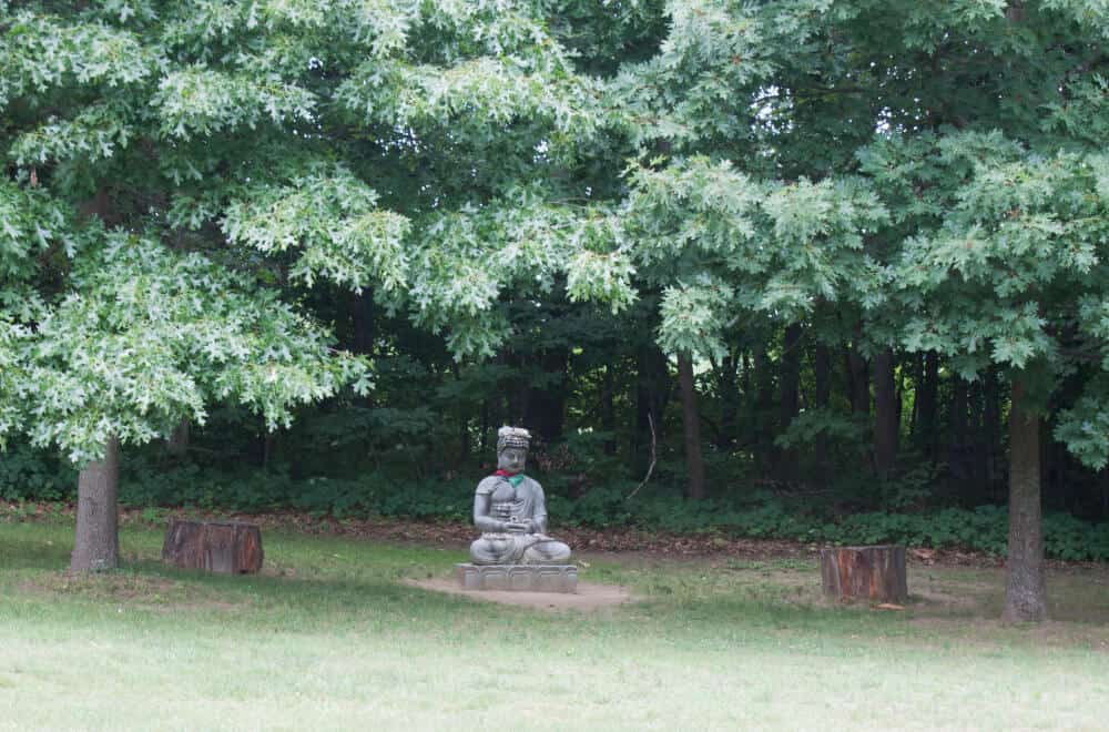 A statue under some trees in the Path of Life Garden, Windsor, VT