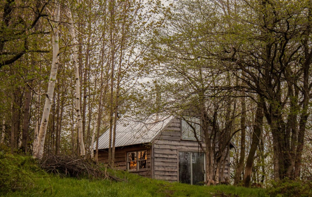 A small cabin nestled in the woods on Stony Pond Farm in Vermont