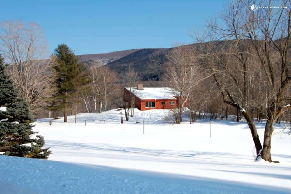 A large cabin surrounded by snow in Manchester, Vermont. For rent on Glamping Hub.