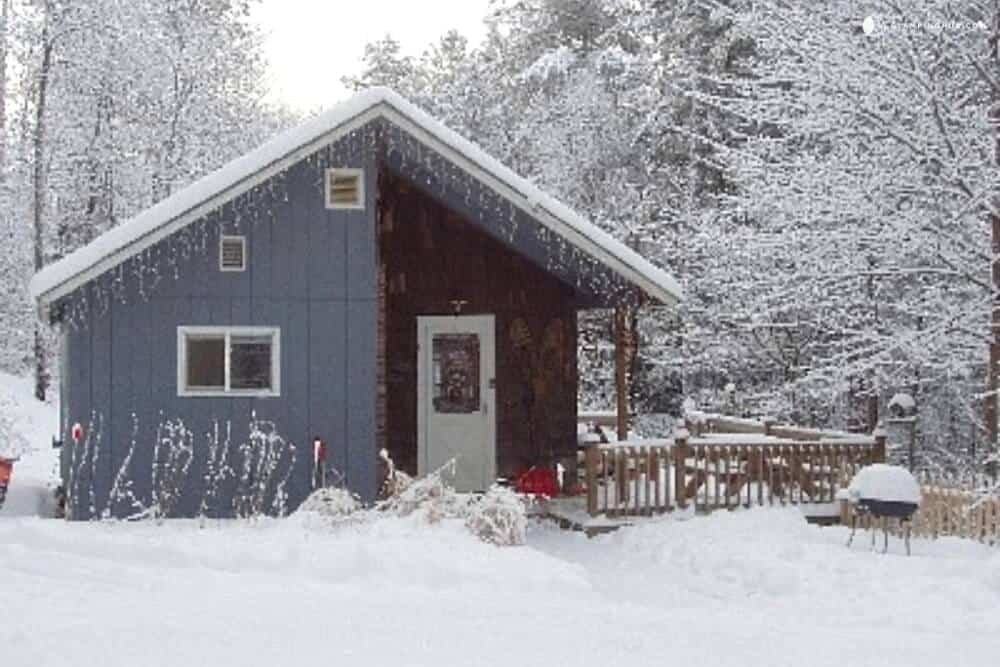 A small blue cottage covered with snow in the White Mountains of New Hampshire.
