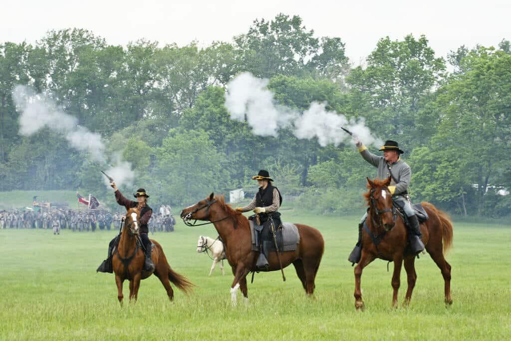 Three men is Civil War dress ride horses during a reenactment