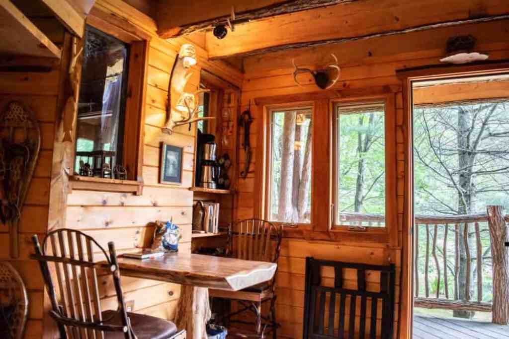 An inside view of our Vermont treehouse rental, with a small table and chairs, a coffee maker, and a picture window.