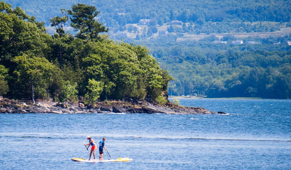 A scene of two stand-up paddleboarders on Lake Champlain in Burton Island State Park
