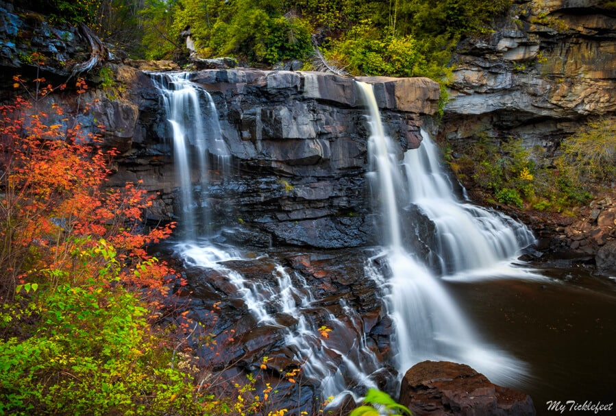 a beautiful waterfall surrounded by fall colors in West Virginia